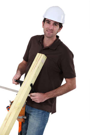 latin man: Builder with wood in a vice