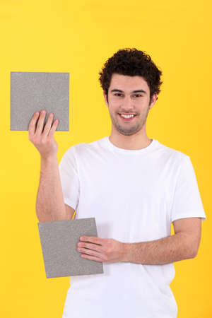 craftsman holding two bathroom tiles photo