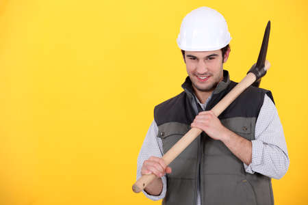 Playful young man holding a pickaxe photo