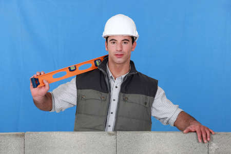 Man stood by wall with spirit-level photo