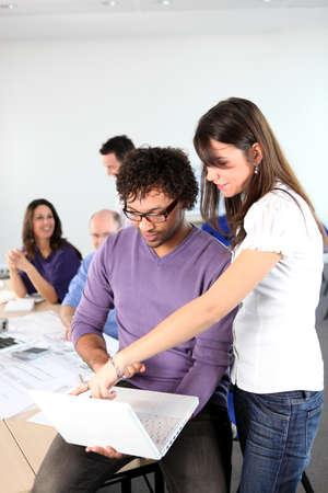 empleados trabajando: Mujer se�alando algo a su colega Foto de archivo