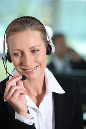 Woman smiling holding headset photo