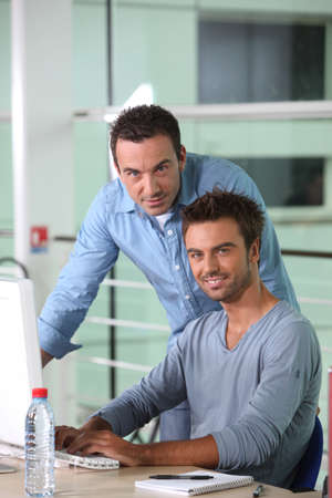 Two men working at a desktop computer Stock Photo - 11456914