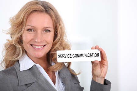 agreeable: Woman in a suit holding a Service Communication sign