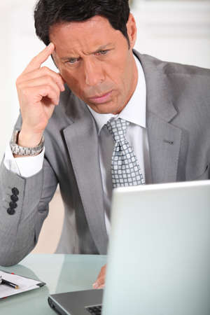 bewilder: Businessman with a puzzled expression looking at a computer screen