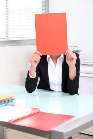 disappeared: Smart woman hiding behind folder