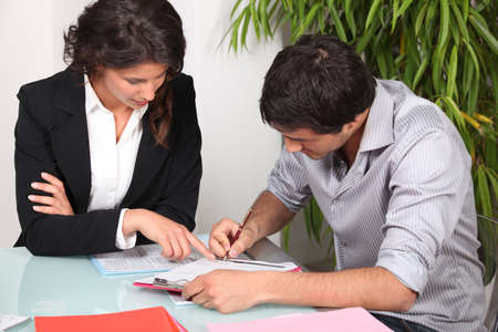 Businesswoman helping her client fill in paperwork Stock Photo