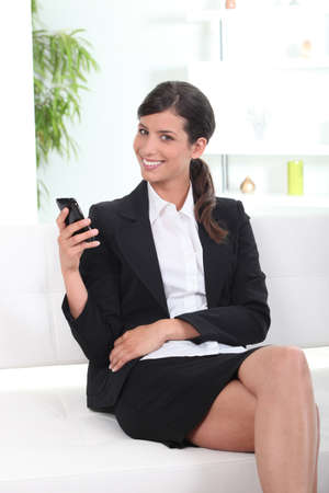 Smiling young businesswoman using cellphone photo
