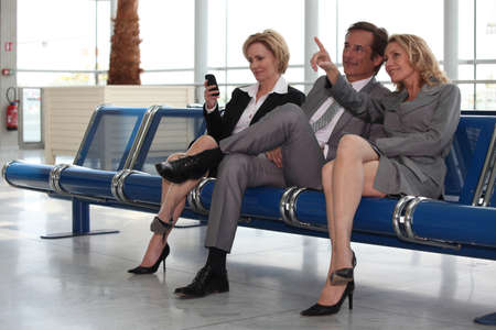 send sms: Businessmen and women in departure lounge.