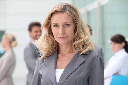magabiztos: Nő, álló, elülső kollégái Stock fotó