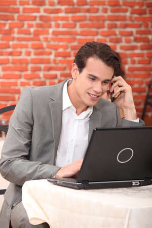 Young man using a laptop in a restaurant photo