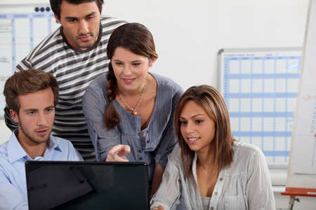 Young people gathered round a laptop Stock Photo - 11456565