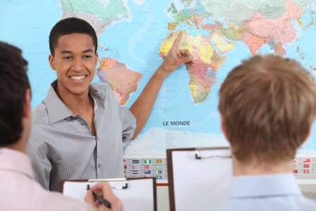 one person with others: Teacher in geography class Stock Photo