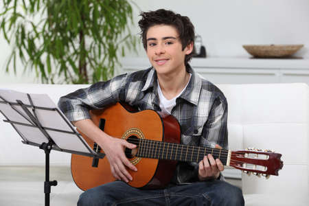 man playing guitar: A young boy learning guitar.