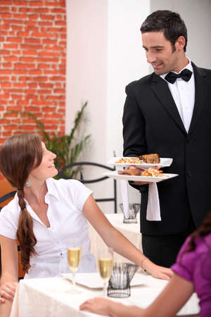 waiter serving: waiter serving a table Stock Photo