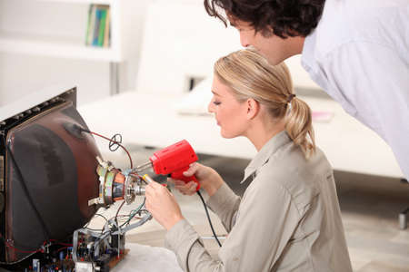 telly: Woman repairing television Stock Photo