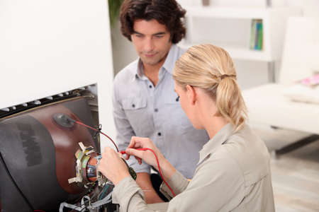 Couple repairing old television Stock Photo - 11457187