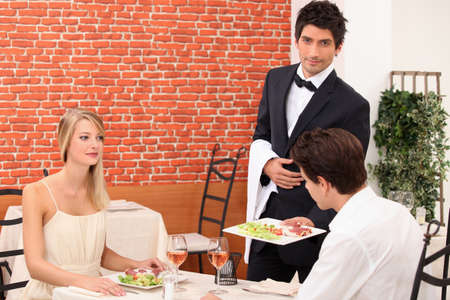 Waiter serving a young couple Stock Photo - 11456887