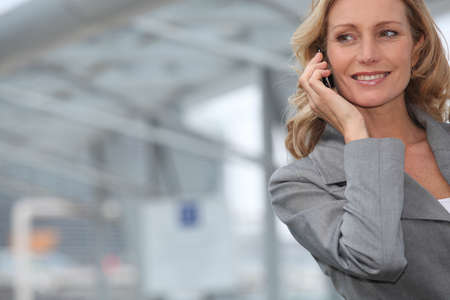 business woman phone: Businesswoman smiling on mobile phone