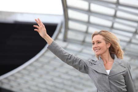 stopping: Businesswoman waving