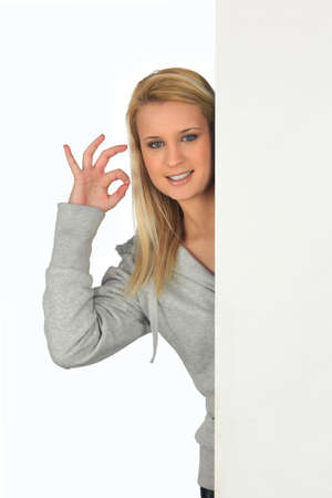 concurrence: Young woman giving the okay sign