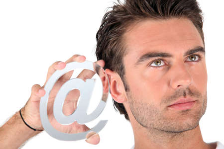 hooked up: Man holding an @ sign Stock Photo
