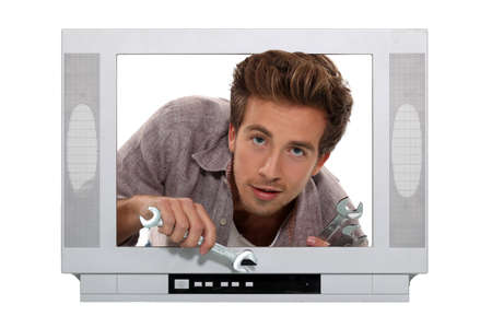 telly: Concept shot of a young man trying to fix a television