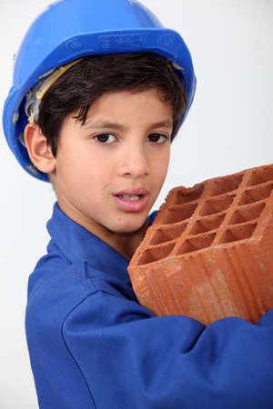Little boy carrying brick photo