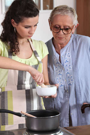Woman using a pestle and mortar in the kitchen photo