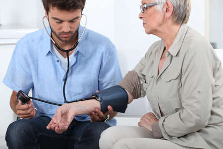 blood pressure cuff: Doctor taking the blood pressure of a patient Stock Photo
