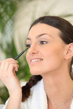 Woman applying eyeliner photo