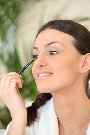 applicator: Woman applying eyeliner