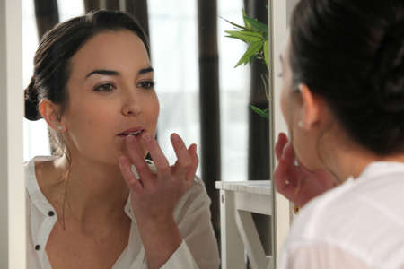 Woman applying lip gloss in a mirror photo