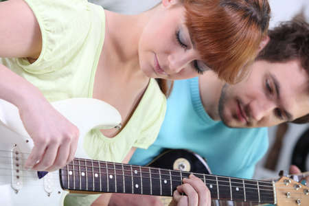 Teenagers with guitar indoors photo