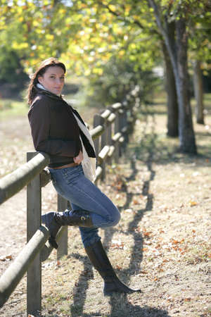 knees bent: Woman leaning against wooden fence