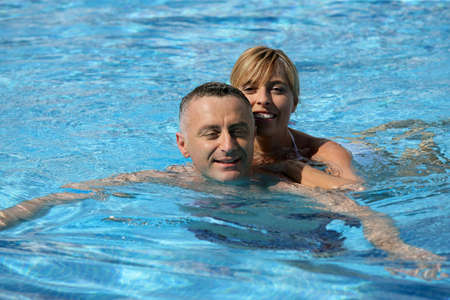 Couple swimming in hotel pool photo