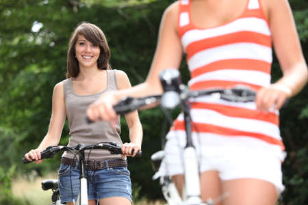 Young women riding bikes photo