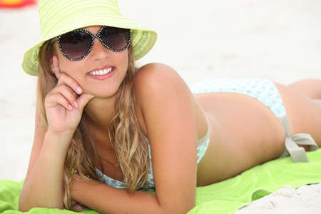 beach wrap: Attractive blond woman sunbathing at the beach