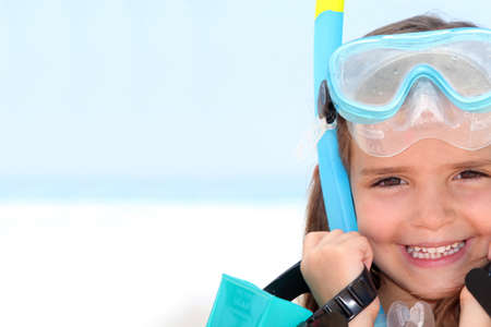 sun from underwater: Little girl wearing snorkel and goggles