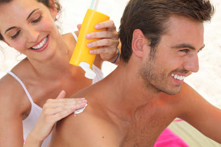 back rub: Couple applying suncream
