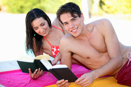 Couple reading books on the beach photo