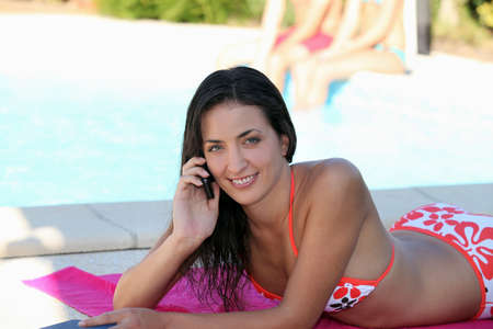 laze: Attractive woman talking on her mobile phone by the poolside