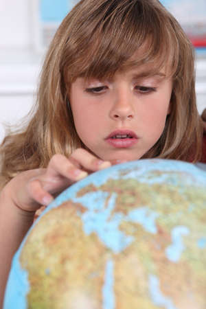schoolkid search: Young girl examining a globe