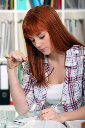 A young red-hair studying for exams. photo