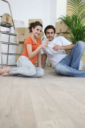 Couple sat on flooring toasting photo