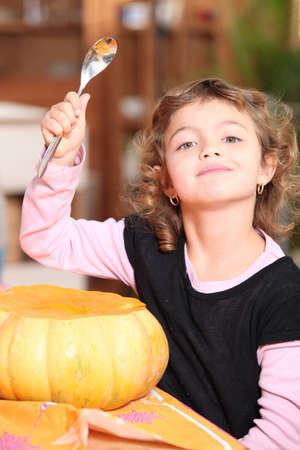 young girl carving a pumpkin photo