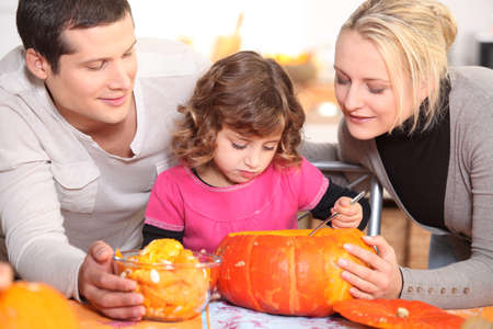 Family carving a pumpkin photo