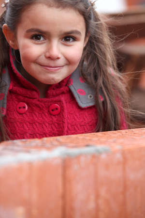 Little girl stood by brick wall photo