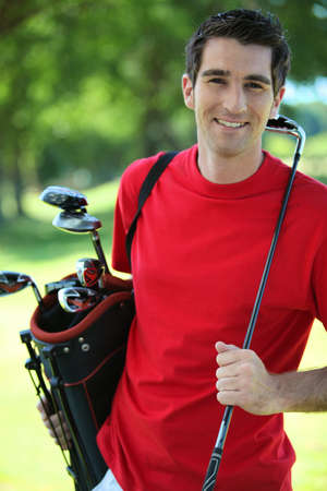 golfers: Golfer carrying clubs. Stock Photo