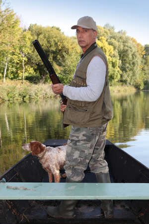 Hunter in a boat with a spaniel and a shotgun photo